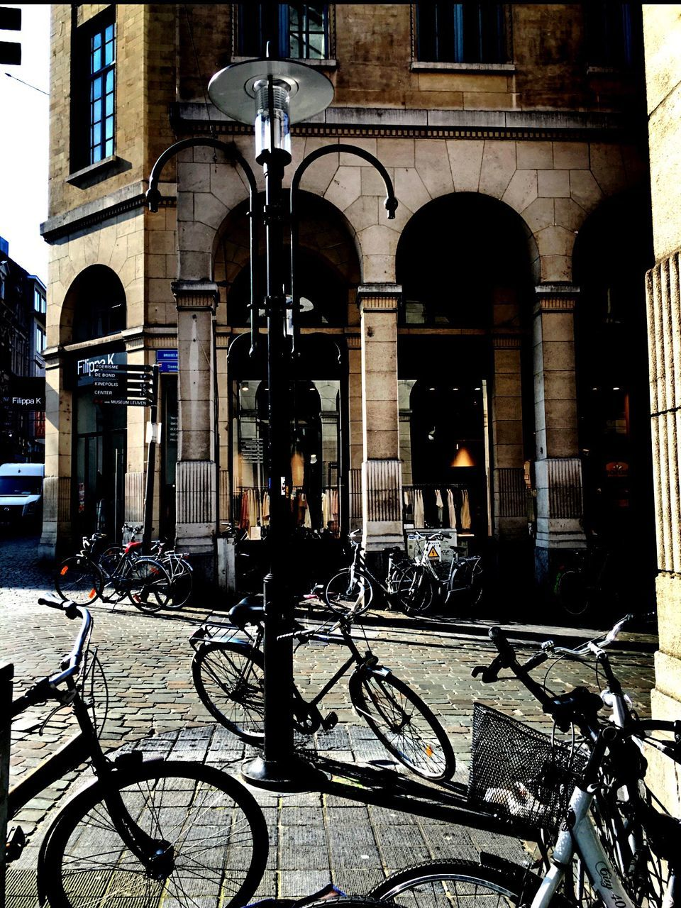 bicycle, architecture, building exterior, built structure, transportation, arch, architectural column, mode of transport, land vehicle, outdoors, stationary, city, day, bicycle rack, no people