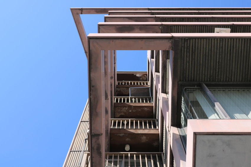 Upwards Angles And Lines Architecture Blue Building Exterior Built Structure City Clear Sky Day Fire Escapes Low Angle View No People Outdoors Railing Sky Staircase Staircase Vertigo Stairs Upwards The Graphic City