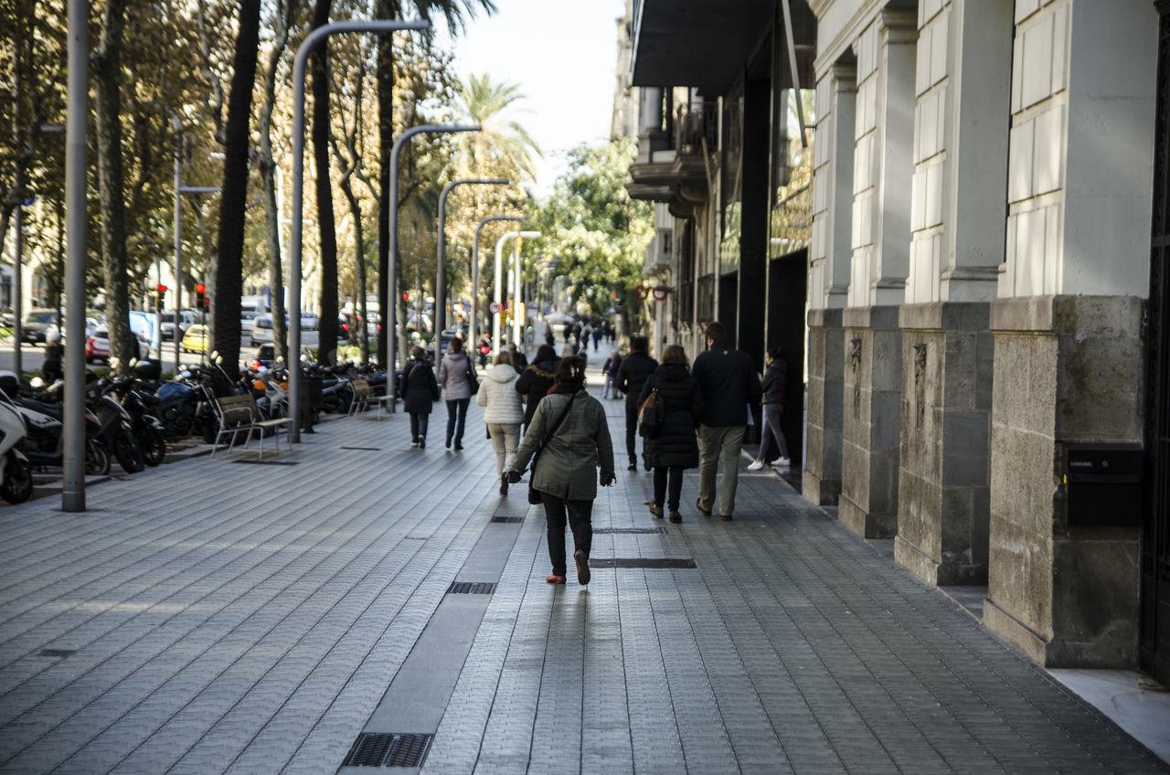 People Walking On Sidewalk In City