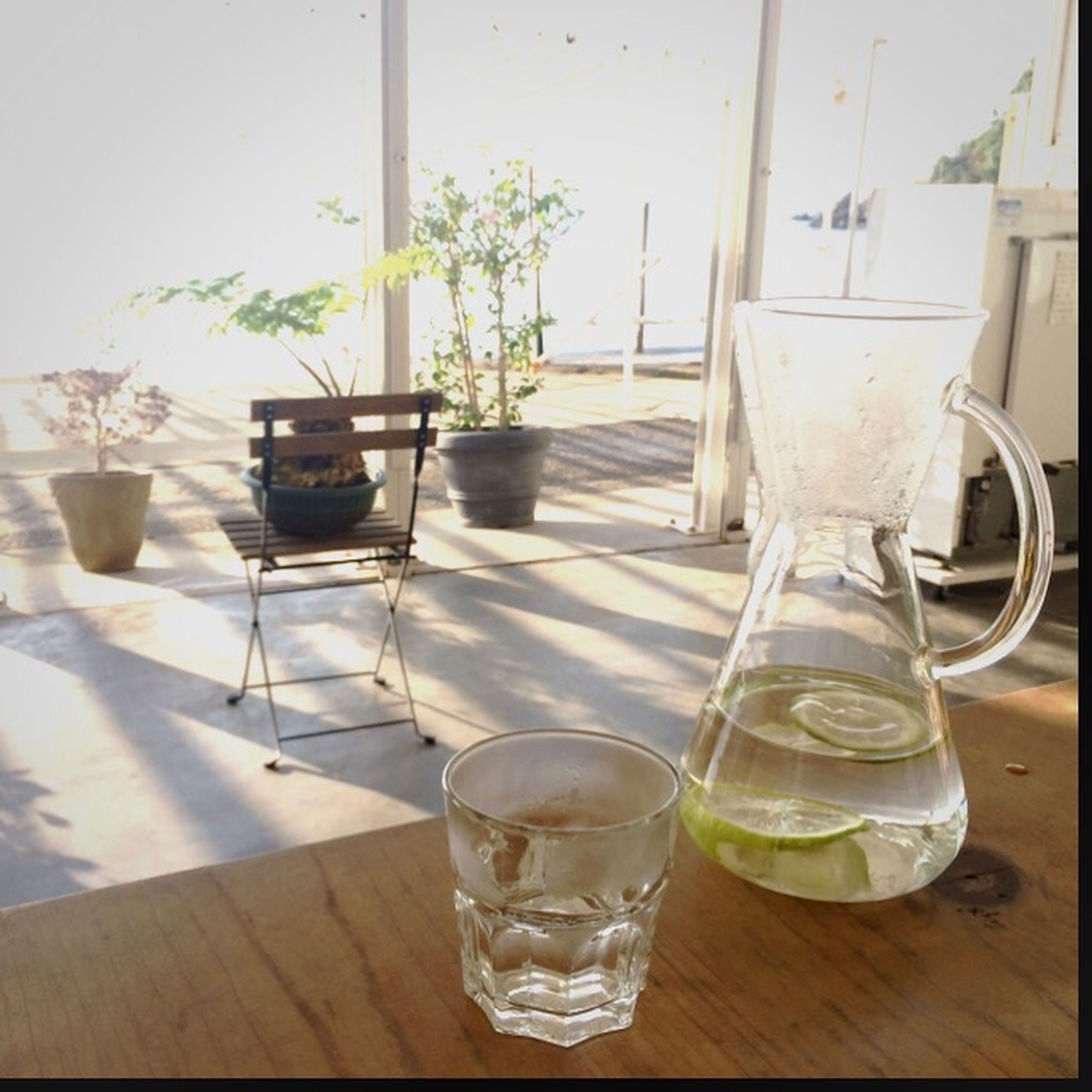 table, indoors, drinking glass, drink, glass - material, transparent, refreshment, still life, vase, freshness, empty, glass, food and drink, absence, chair, home interior, window, wineglass, wood - material, sunlight