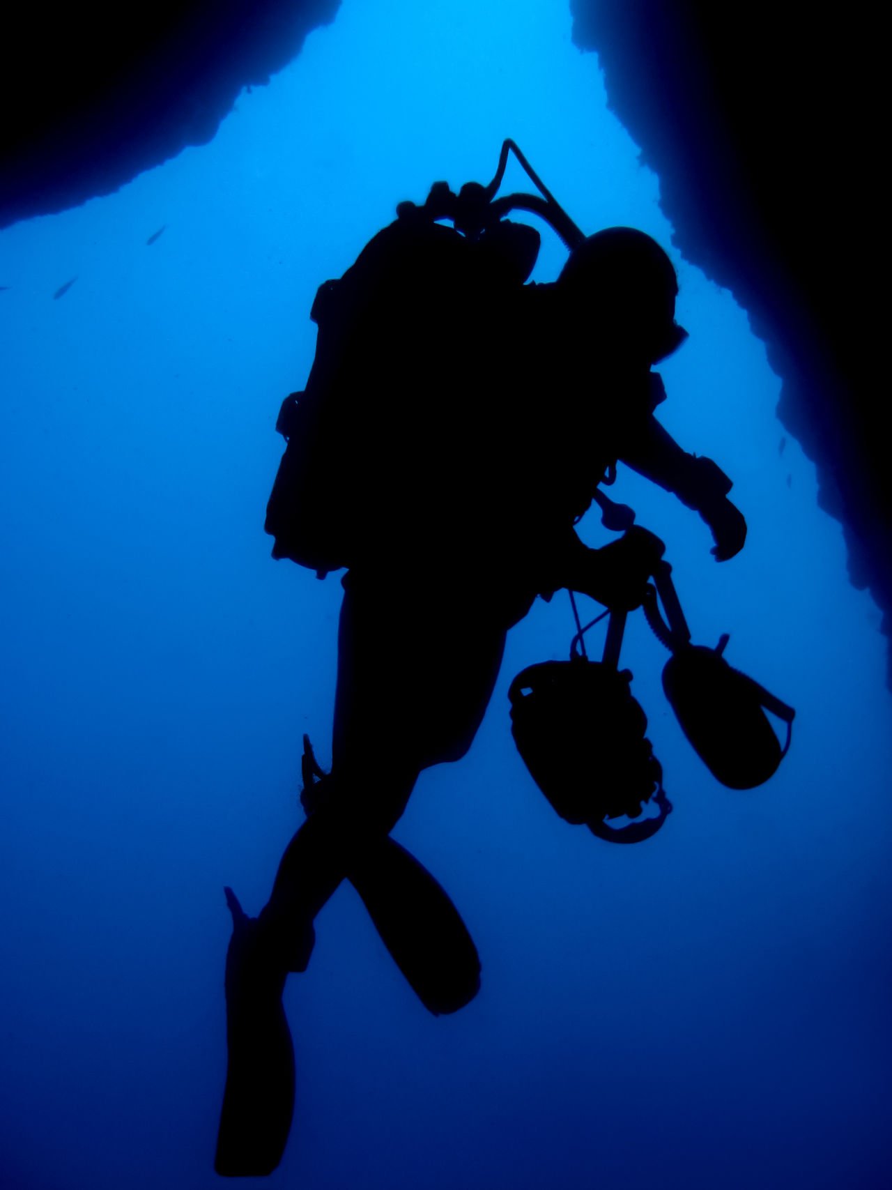 Silhouette of professional underwater photographer in front of underwater cave exit Cave Equipement Photography Proffesional SCUBA Scuba Diver Scubadiving Silhouette Underwater Underwater Photographer Underwater Photography