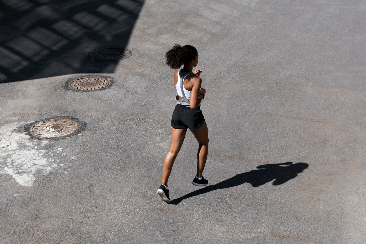 Adult Adults Only Athlete Day Fitness Full Length Healthy Lifestyle High Angle View Jogging Mixed Race One Person One Woman Only One Young Woman Only Only Women Outdoors People Runner Shadow Sport Street Urban Young Adult