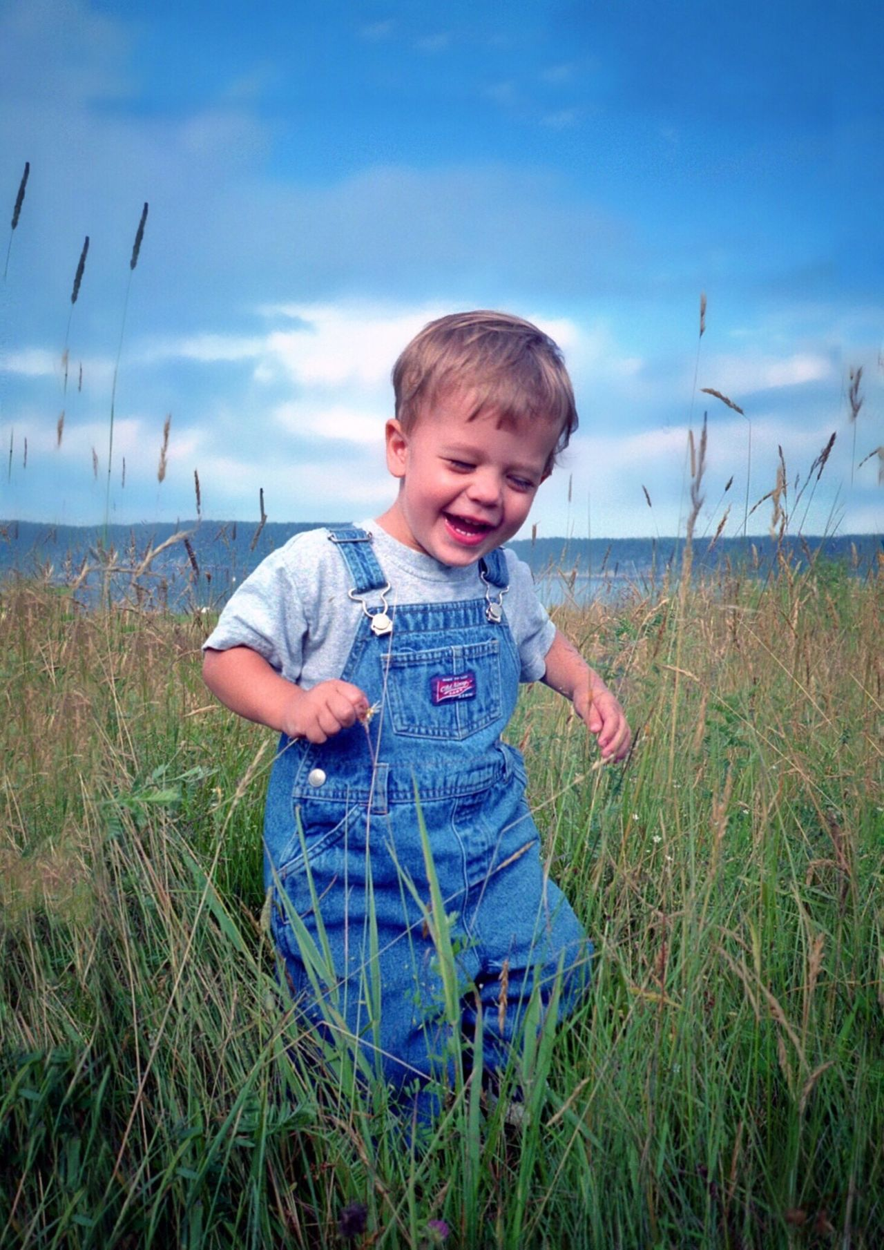 Happy Spring! Sunshine Blue Sky Happy Boy Boy In Field Boy In Overalls Childhood Green Green Grass Blue Smile Happy Child  Play Playing The Essence Of Summer The Portraitist - 2016 EyeEm Awards Maine Live For The Story