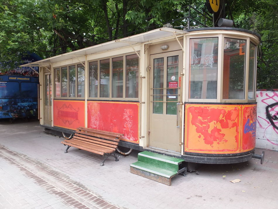 Old Trolley Bus on Arabil Street Cafe Capital City City Composition Empty Full Frame Fun History Moscow No People Old Orange Color Outdoor Photography Parked Russia Stationary Street Tourism Tourist Attraction  Tourist Destination Tree Trolley Bus Unusual